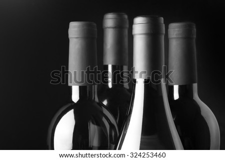 Four assorted wine bottles close-up on black background. Monochrome black and white image. Focus on front bottle. - stock photo