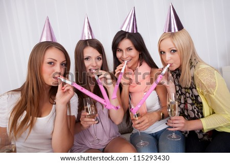 Four attractive females celebrating with a champagne and cone caps - stock photo