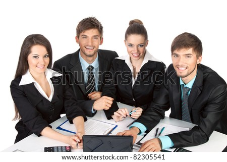 four attractive positive smile young business people in elegant suits sitting at desk in front of a laptop computer with papers, document working in team together, Isolated over white background - stock photo
