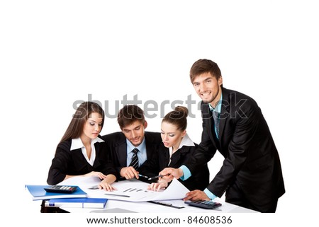 four attractive positive young business people in elegant suits sitting at desk working in team together and discussing the problem Isolated over white background
