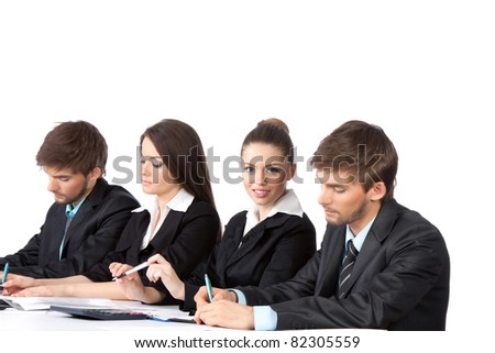 four attractive positive young business people sitting in row at desk working in team together, writing lecture, paper work, Isolated over white background, concept of  training lecture conference - stock photo