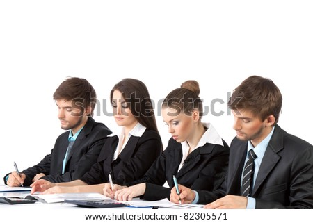four attractive positive young business people sitting in row at desk working in team together, writing lecture, paper work, Isolated over white background, concept of  training lecture conference
