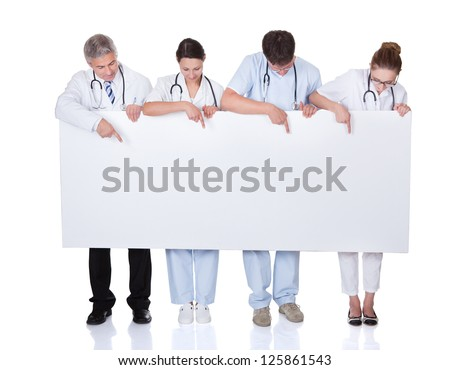 Four attractive professional diverse medical staff holding up a long horizontal blank white banner for your text or advertisement