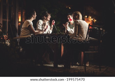 Four attractive women night out having dinner in a restaurant  - stock photo
