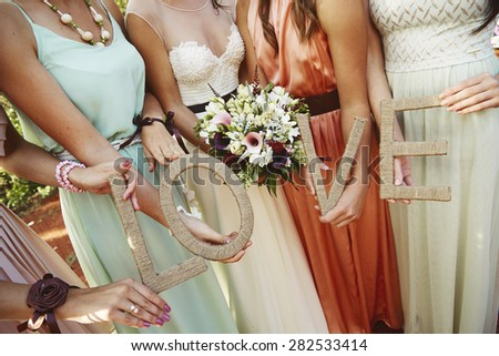 Four attractive young and beautiful girl in dress on a summer day holding love letter. - stock photo