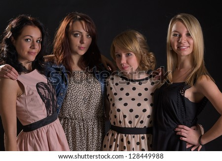Four attractive young women on an evening out together standing arm in arm in the darkness smiling happily at the camera - stock photo