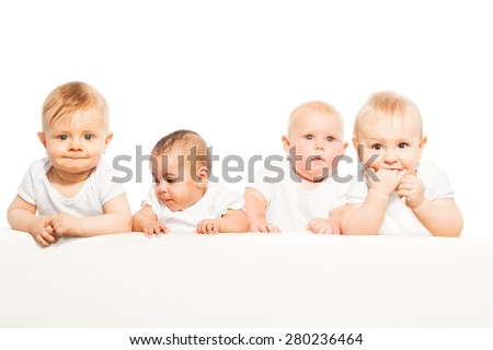 Four babies stand in a row on the white background - stock photo
