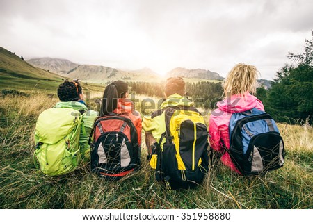 Four backpackers looking at sunset over the mountains - Hikers talking and relaxing after an excursion in the nature - Friends enjoying winter holiday - stock photo