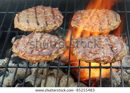 four barbecue hamburgers with flames - stock photo