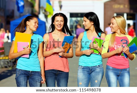four beautiful college girls walking on the street - stock photo