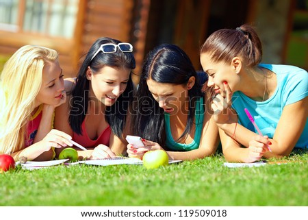 four beautiful girls chatting in social network on green lawn