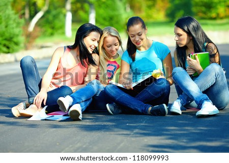 four beautiful girls friends read books, sitting on the ground