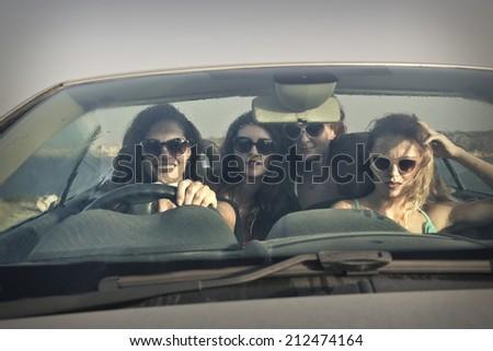four beautiful girls in a car - stock photo