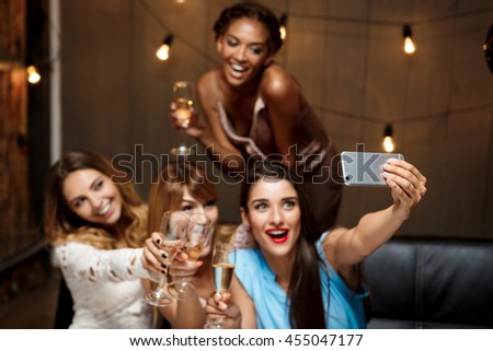 Four beautiful girls making selfie at party.