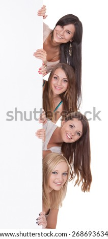 Four beautiful long-haired women peering around the edge at a blank sign with copyspace for your text