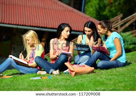 four beautiful students girls prepare for the exam on green lawn - stock photo