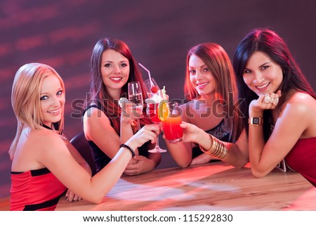 Four beautiful young female friends enjoying a cocktail seated at a table in a nightclub - stock photo