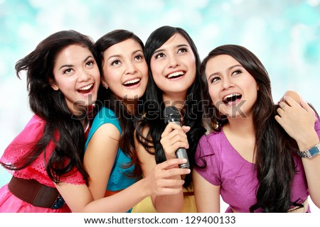 Four beautiful young woman singing karaoke together