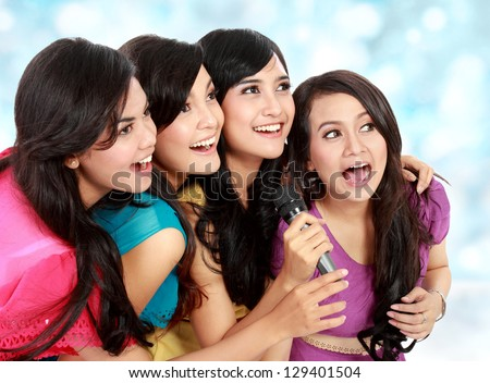 Four beautiful young woman singing karaoke together - stock photo