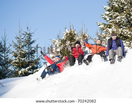 Four best friends sliding on the snow - stock photo