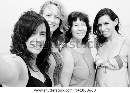 four best girlfriends making selfie-photo at seaside - stock photo
