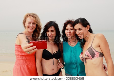 four best girlfriends walking at seaside - stock photo