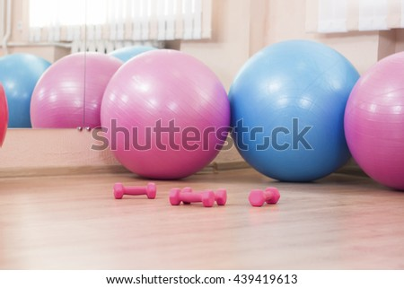 Four Big Fitballs and Barbells On Floor in Sport Fitness Center Indoors. Horizontal Image Orientation