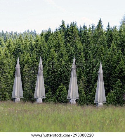 four big military missiles hidden in forests ready to be launched - stock photo