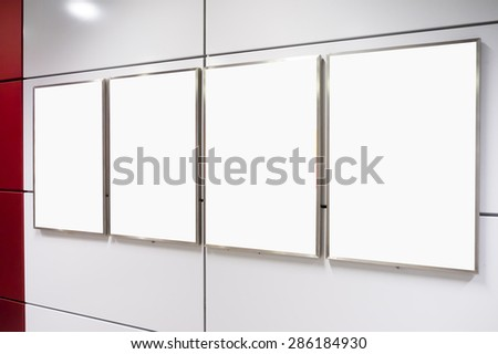 Four big vertical / portrait orientation blank billboard on modern white wall - stock photo