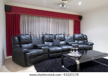 Four black executive leather home theater chairs with wine glasses on tray on black table and red curtains