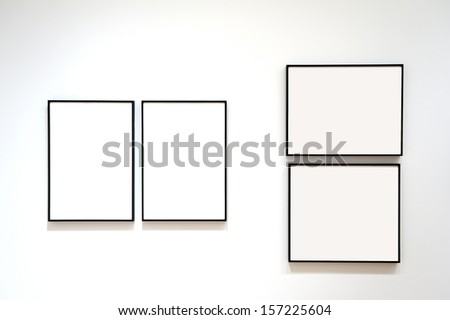 Four blank frames on a white wall - stock photo
