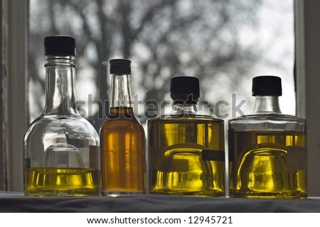 Four bottle of olive oil at the window