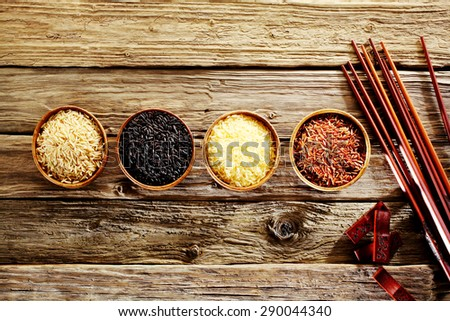 Four bowls of different varieties of rice with basmati, wild rice, long grain and red rice with a set of bamboo chopsticks depicting Asian cuisine on a rustic weathered wood background - stock photo