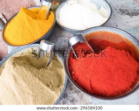 Four bowls of Indian spices on a market including turmeric, cumin and hot chili powder - stock photo