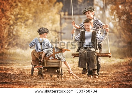 Four boys on a swing, and ride a bike on the playground in the shade of a summer day - stock photo