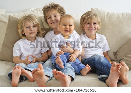Four brothers, young boys, sitting on a sofa. The eldest is holding a baby in his lap.  They're looking to the right of camera - stock photo
