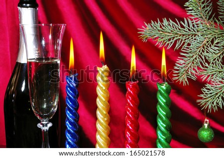 Four burning candle, goblet of champagne and bottle against purple drapery - stock photo