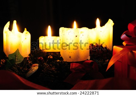 Four burning candles and gift packet on the black background - stock photo