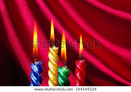 Four burning christmas candles against purple drapery - stock photo