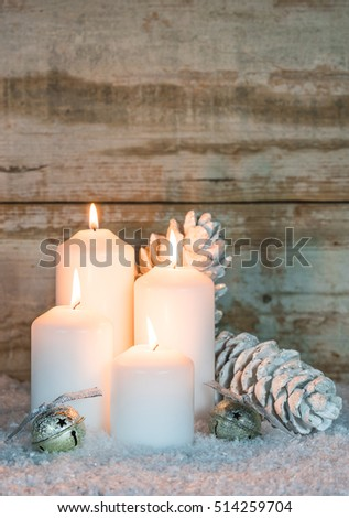 Four burning Christmas candles with fir cones and bells in snow