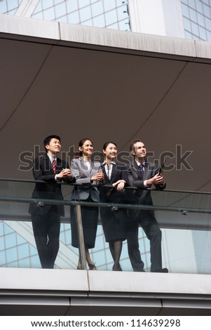 Four Business Colleagues Having Discussion Outside Office Building - stock photo