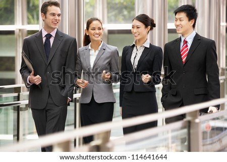 Four Business Colleagues Having Discussion Whilst Walking Outside Office
