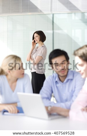 Four business colleagues holding a meeting, one talking on mobile phone