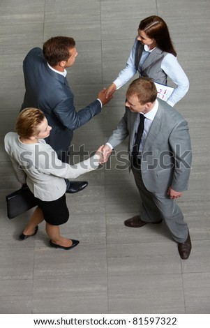 Four business partners handshaking while striking deal