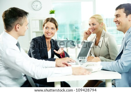 Four business partners sitting in office and interacting at meeting - stock photo