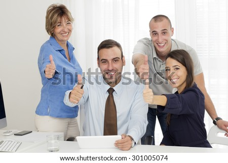Four business people  around the table with thumb up  happily looking at camera. - stock photo