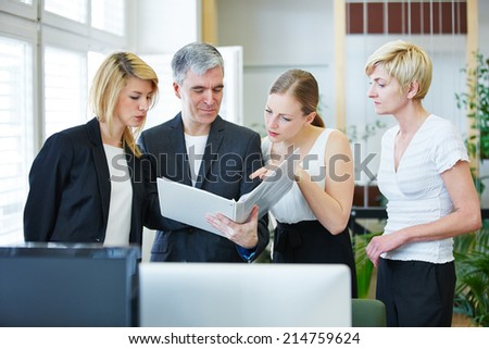 Four business people in the office discussing a file in a meeting - stock photo