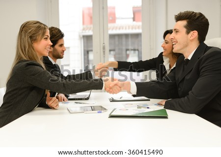 Four business people shaking hands, finishing up a meeting  - stock photo