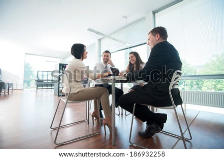 Four business people sitting around office table - stock photo
