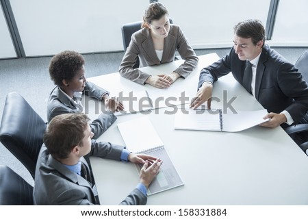 Four business people sitting around table and having business meeting